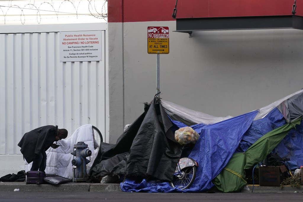 FILE - In this Nov. 21, 2020, file photo, a man stands near tents set up on a sidewalk in San Francisco. When census takers tried to count the nation'...