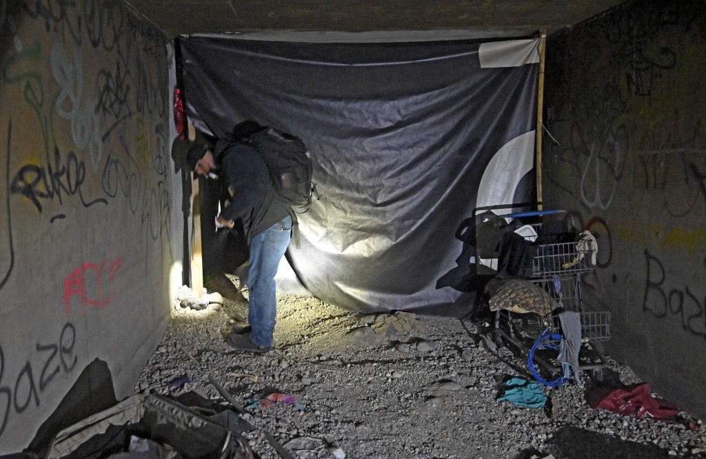 FILE - In this Dec. 5, 2020, file photo, Paul Vautrinot of Shine a Light passes though personal belongs as he provides outreach in the underground tun...