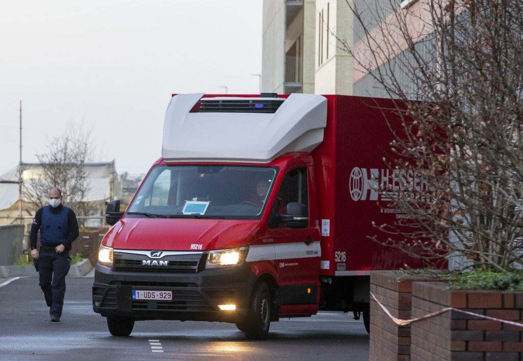 A police officer accompanies a truck delivering part of a Pfizer-BioNTech Covid-19 vaccine at the UZ Leuven hospital in Leuven, Belgium, Saturday, Dec...