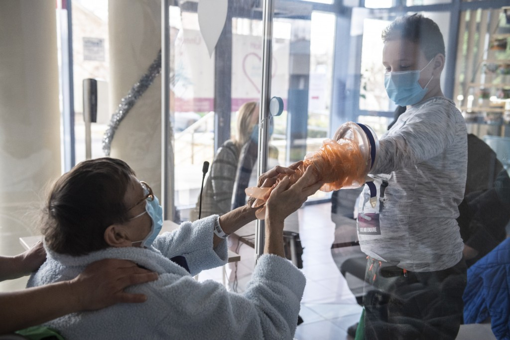 A patient holds the hands of her relative in safe conditions sitting behind a plastic sheet in the so-called Chamber of Our Heart room, which has two ...