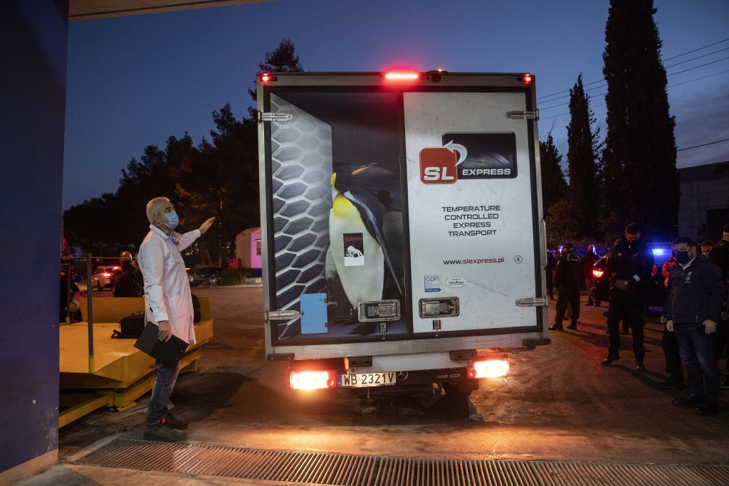 A man instructs the driver of a van, carrying vaccines against COVID-19, to park at a warehouse of a Greek healthcare logistics company at Kryoneri vi...