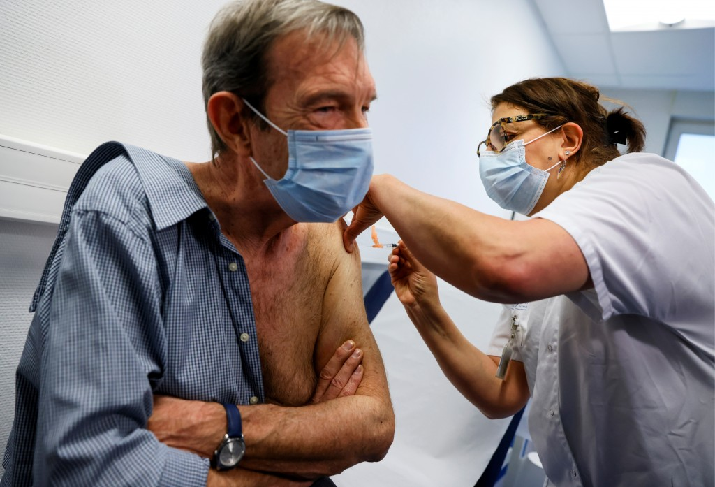 French cardiologist Jean-Jacques Monsuez receives a dose of the Pfizer-BioNTech Covid-19 at the Rene-Muret hospital in Servan near Paris, Sunday Dec. ...