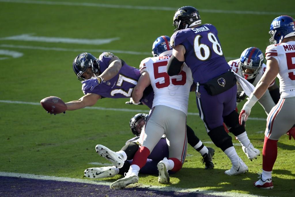 Baltimore Ravens running back J.K. Dobbins (27) dives across the goal line while scoring a touchdown on a run as New York Giants outside linebacker Da...
