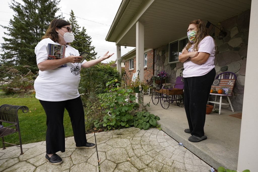 FILE - In this Thursday, Oct. 15, 2020 file photo, Lori Goldman talks with a voter while canvassing in Troy, Mich. In suburban Michigan, a coalition o...