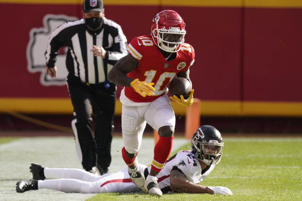 Kansas City Chiefs wide receiver Tyreek Hill runs down the sideline after evading a tackle by Atlanta Falcons A.J. Terrell during an NFL football game...