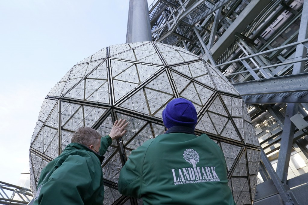 Workers secure a panel of Waterford crystal triangles on the Times Square New Year's Eve ball, Sunday, Dec. 27, 2020, in New York.  (AP Photo/Kathy Wi...