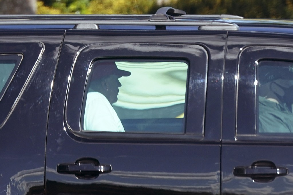 President Donald Trump rides in a motorcade vehicle as he departs Trump International Golf Club, Sunday, Dec. 27, 2020, in West Palm Beach, Fla. (AP P...