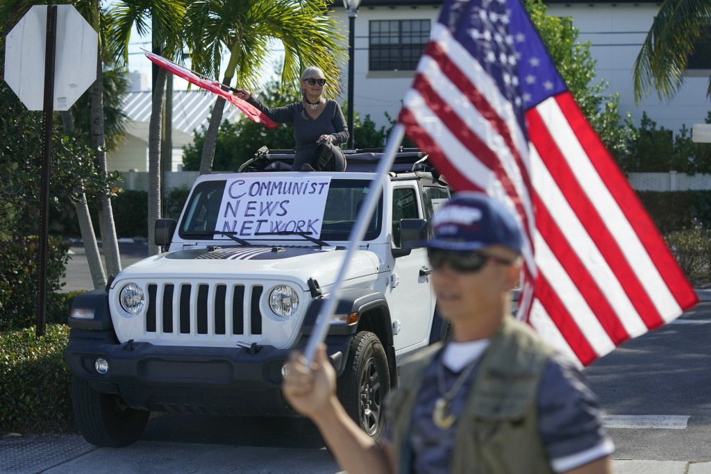 Supporters of President Donald Trump watch his motorcade drive by in West Palm Beach, Fla., Sunday, Dec. 27, 2020. Trump is en route to his Mar-a-Lago...