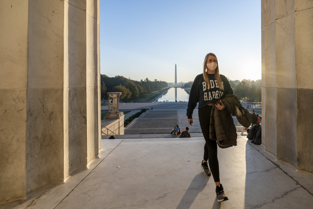 FILE - In this Nov. 8, 2020, file photo, a woman wears a Biden-Harris campaign shirt as she and others gather at the Lincoln Memorial at sunrise, Sund...