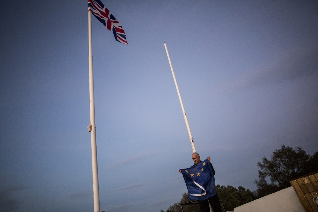 FILE - In this Friday, Jan. 31, 2020 file photo, a worker folds the EU flag after being lowered at the British territory of Gibraltar.  While corks ma...
