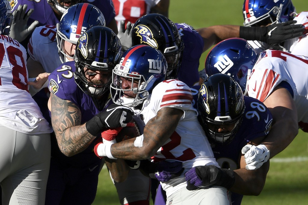 New York Giants running back Wayne Gallman, center, is stopped by Baltimore Ravens defensive end Derek Wolfe (95) and defensive tackle Brandon William...