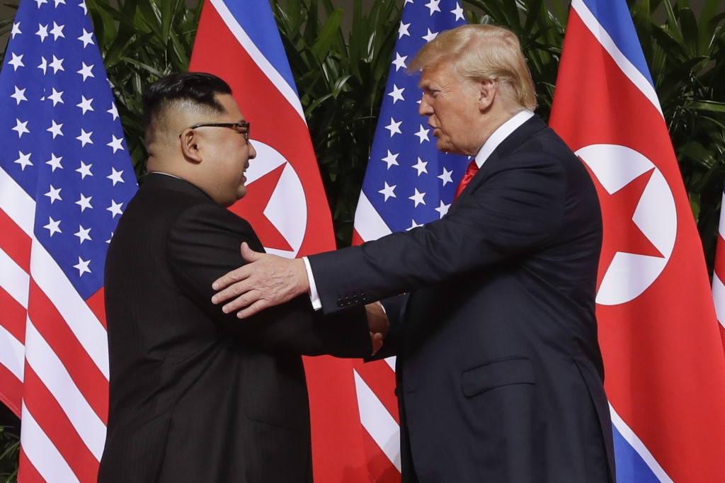 FILE - In this June 12, 2018, file photo, President Donald Trump, right, shakes hands with North Korea leader Kim Jong Un at the Capella resort on Sen...