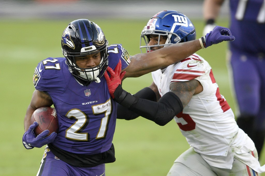 Baltimore Ravens running back J.K. Dobbins (27) is pushed out of bounds by New York Giants free safety Logan Ryan (23) during the second half of an NF...