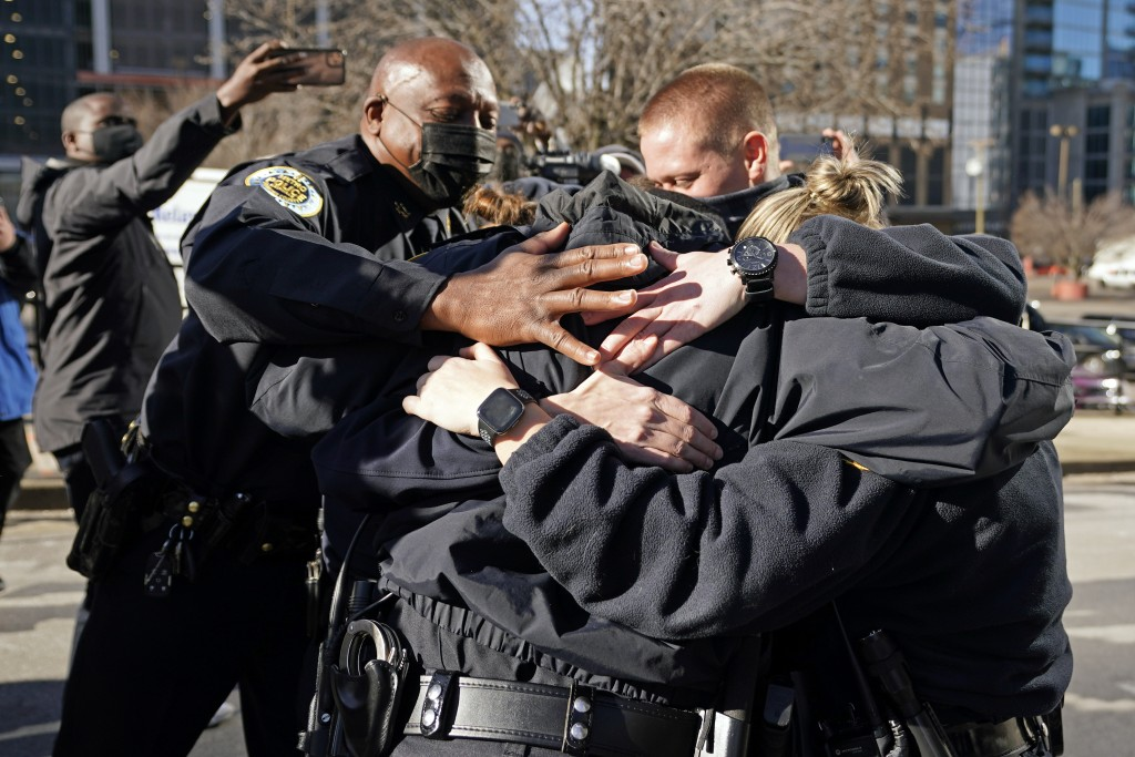 Nashville Police Chief John Drake, left, joins a group of police officers as they embrace after speaking at a news conference Sunday, Dec. 27, 2020, i...