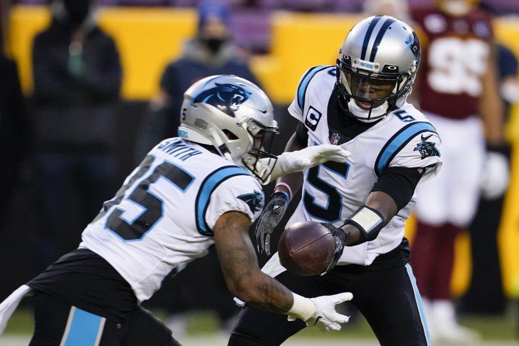 Carolina Panthers quarterback Teddy Bridgewater (5) hands the ball off to running back Rodney Smith (35) during the first half of an NFL football game...