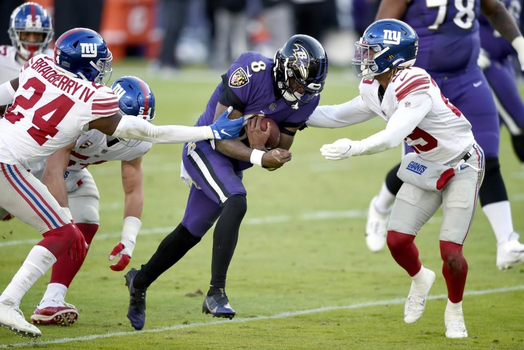 Baltimore Ravens quarterback Lamar Jackson (8) runs with the ball as New York Giants cornerback James Bradberry (24) and safety Xavier McKinney (29) t...
