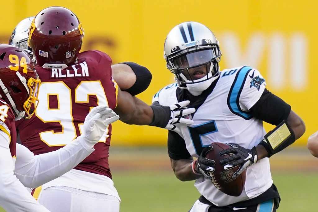 Carolina Panthers quarterback Teddy Bridgewater (5) moves around the reach of Washington Football Team defensive tackle Jonathan Allen (93) during the...