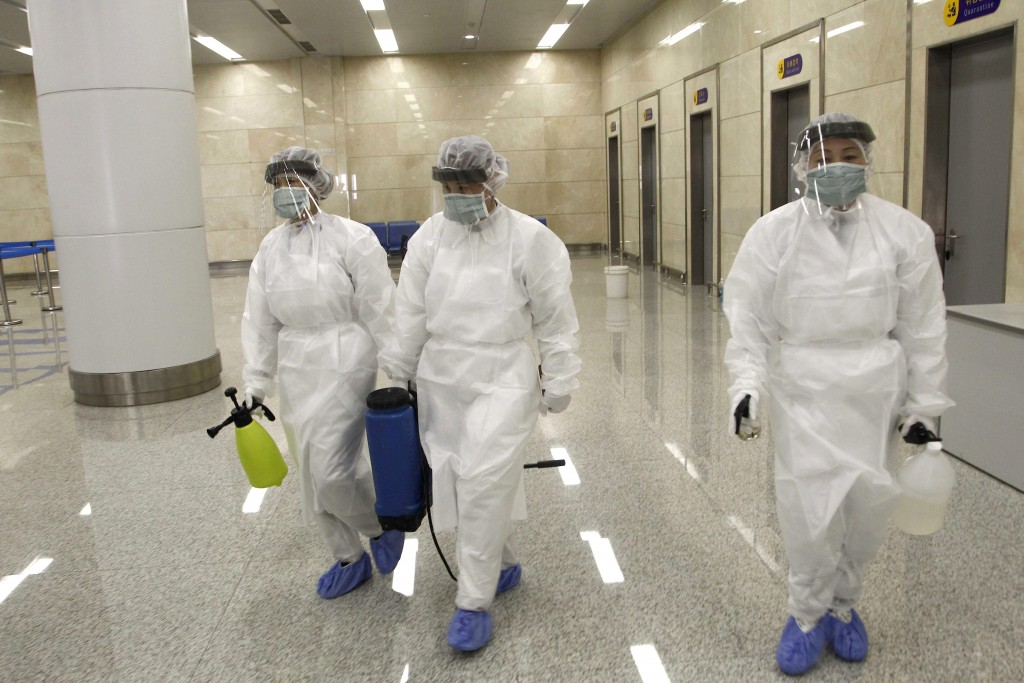 FILE - In this Feb. 1, 2020, file photo, State Commission of Quality Management staff armed with protective gear and disinfectant, prepare to check th...