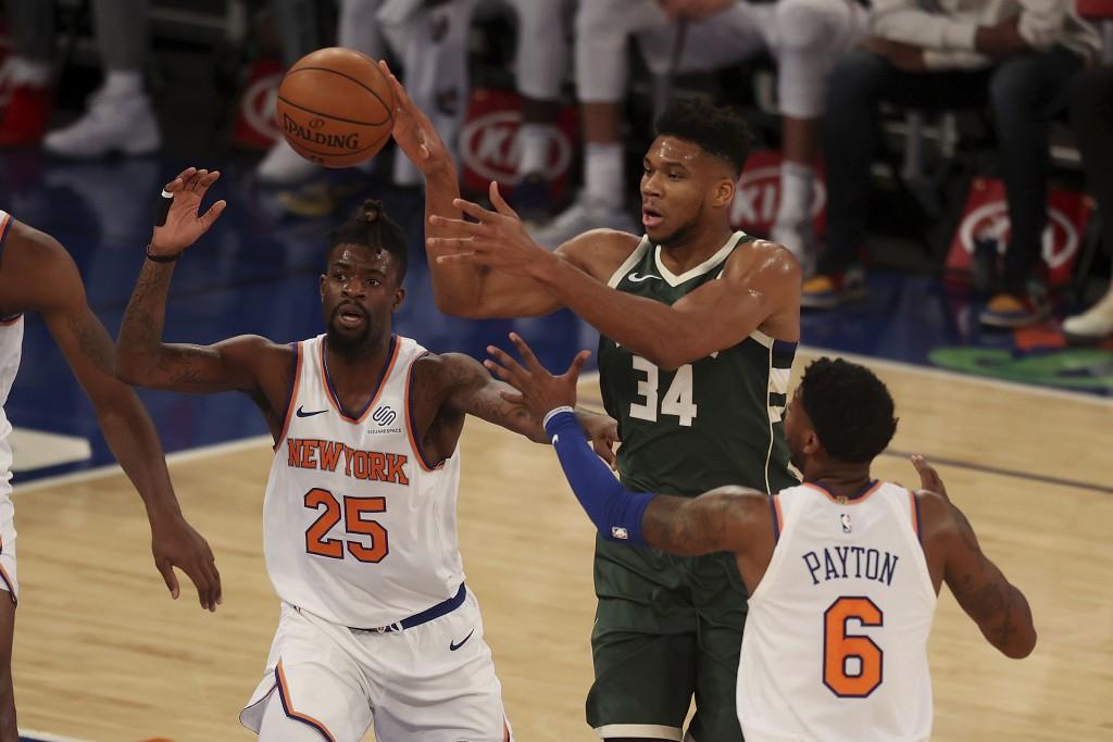 Giannis Antetokounmpo, center, of the Milwaukee Bucks passes the ball against Reggie Bullock, left, of the New York Knicks at Madison Square Garden on...