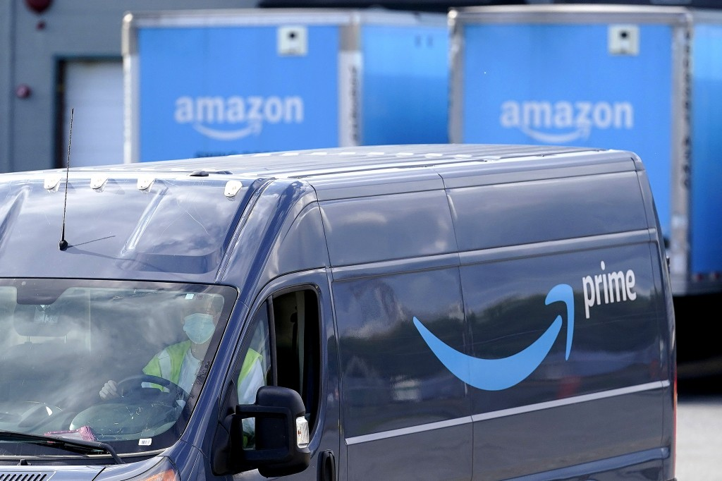 FILE - In this Oct. 1, 2020 file photo, an Amazon Prime logo appears on the side of a delivery van as it departs an Amazon Warehouse location in Dedha...