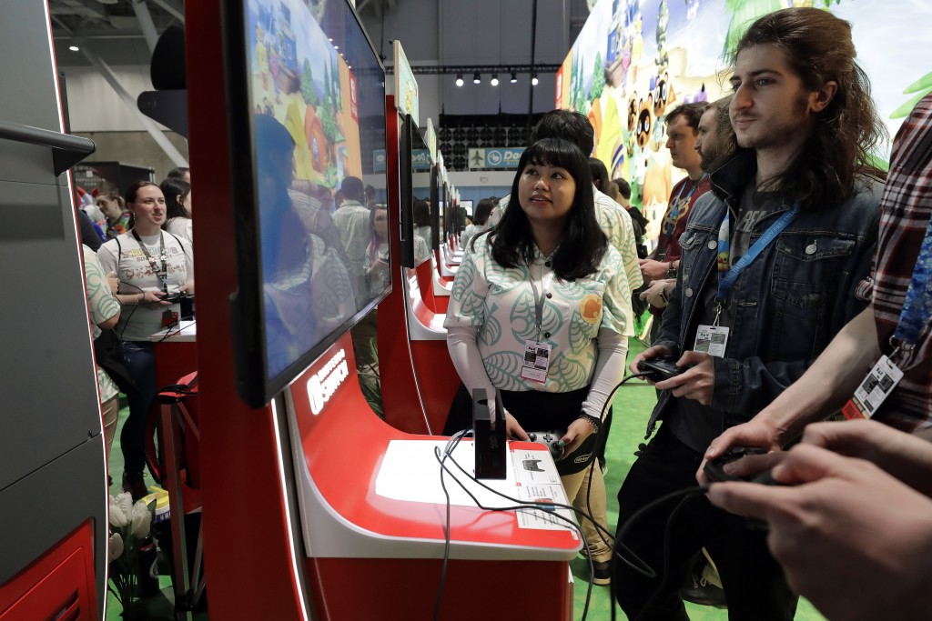 FILE - Visitors to the Pax East conference play the new Nintendo Switch video game Animal Crossing, Thursday, Feb. 27, 2020, in Boston. Thousands of g...