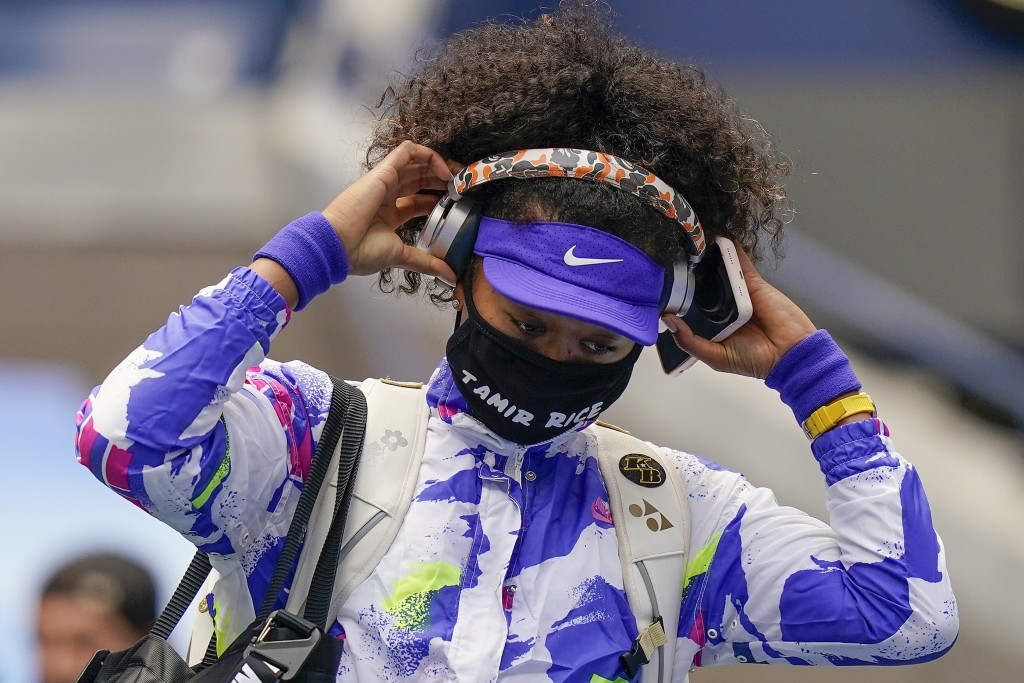 FILE - In this Sept. 12, 2020, file photo, Naomi Osaka, of Japan, pulls off her headphones as she walks on the court before playing against Victoria A...