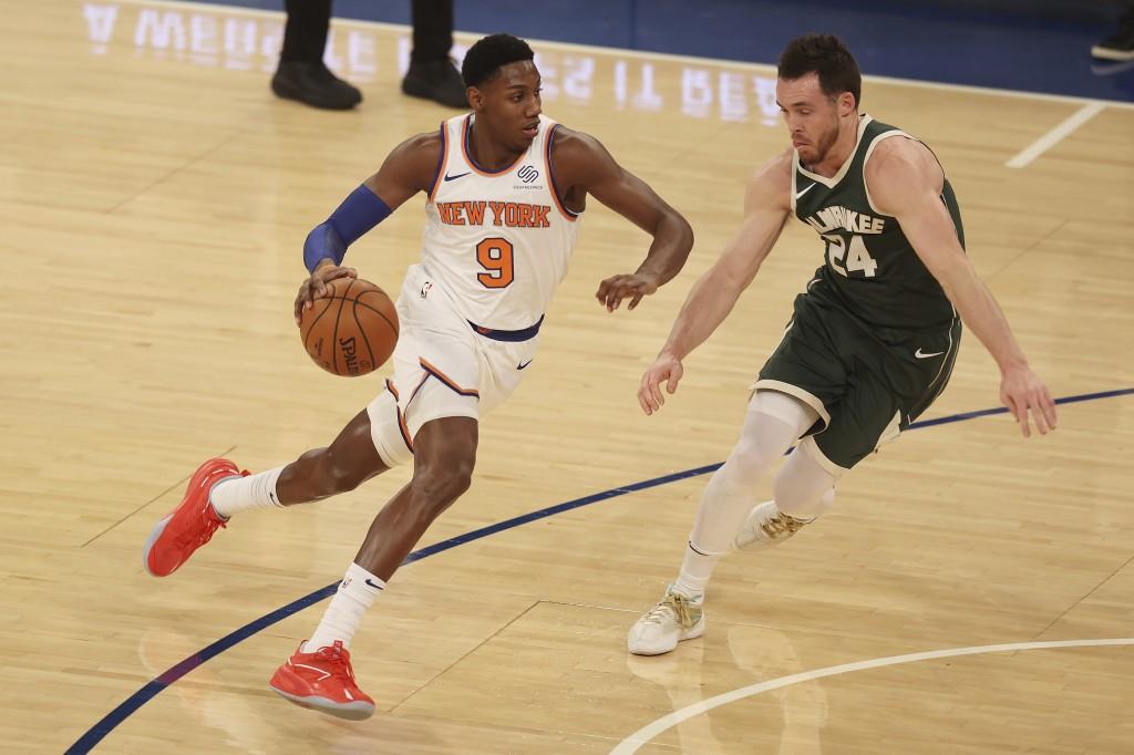 RJ Barrett, left, of the New York Knicks drives towards the basket against Pat Connaughton, right, of the Milwaukee Bucks at Madison Square Garden on ...
