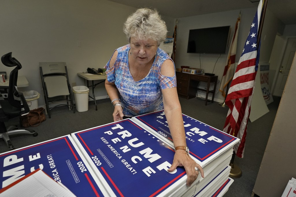 FILE - In this Tuesday, Sept. 8, 2020 file phto, Pamela Allen organizes Trump-Pence campaign signs at the Pasco county GOP headquarters in Hudson, Fla...