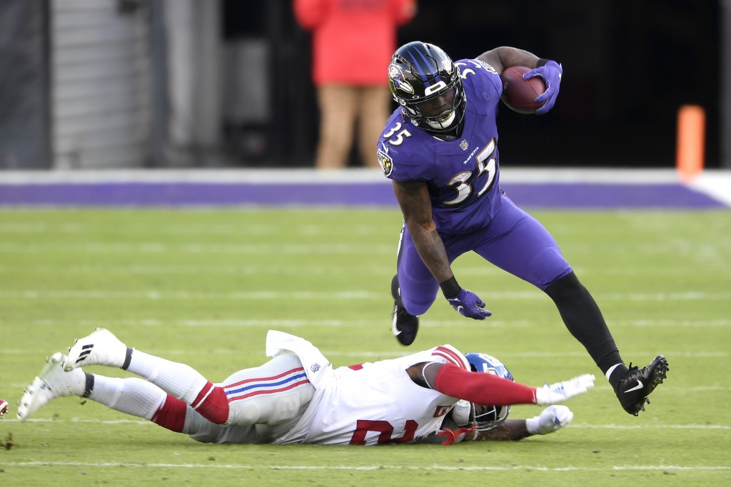 Baltimore Ravens running back Gus Edwards (35) avoids a tackle by New York Giants strong safety Jabrill Peppers (21) during the first half of an NFL f...