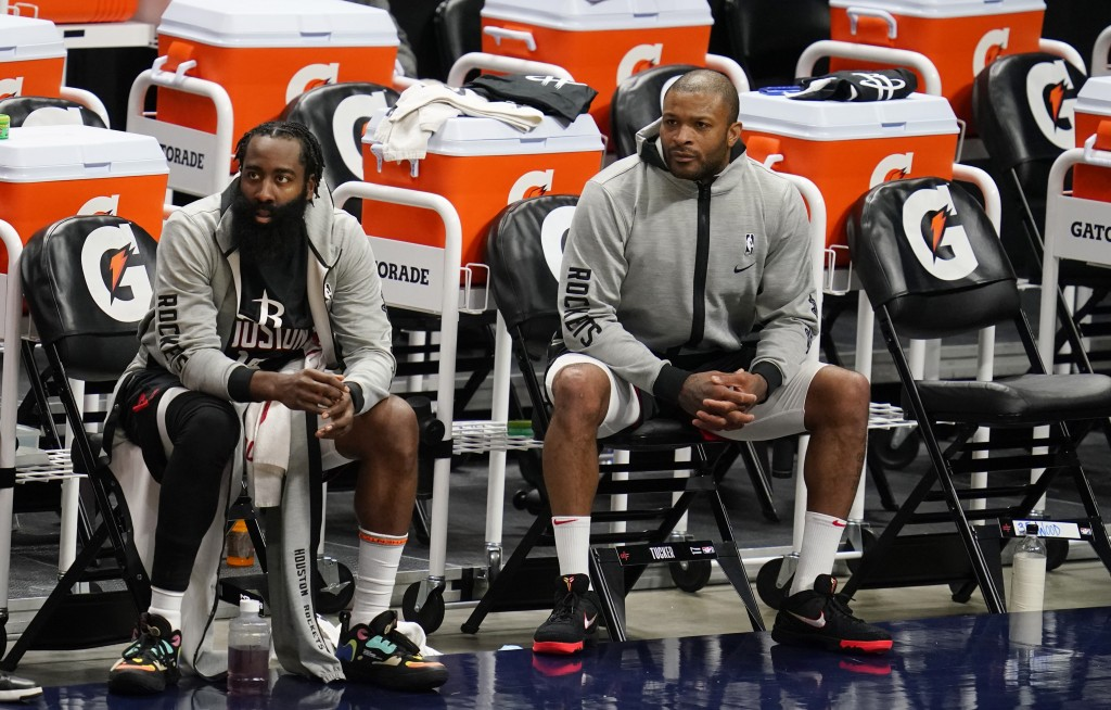 Houston Rockets guard James Harden, left, and forward P.J. Tucker watch from the bench during the second half of the team's NBA basketball game agains...
