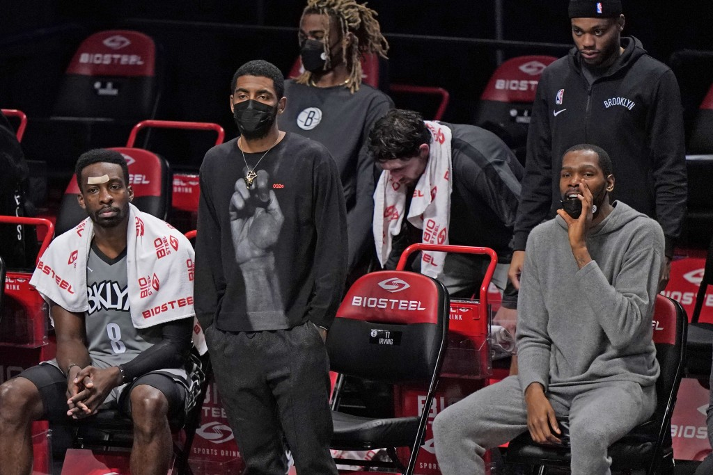 Brooklyn Nets forward Jeff Green (8), guard Kyrie Irving and forward Kevin Durant, from left, watch from the bench during the first half of the team's...