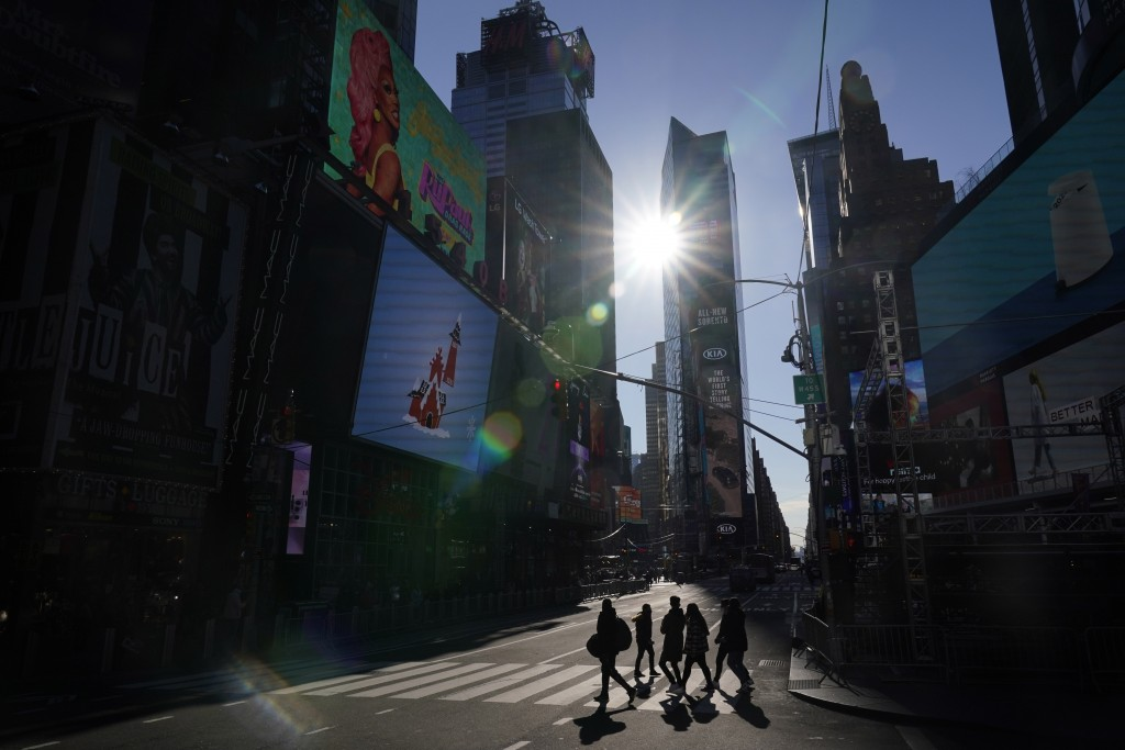 A few pedestrians make their way across a lightly trafficked intersection in Times Square, New York, Monday, Dec. 28, 2020. While there will be a ball...