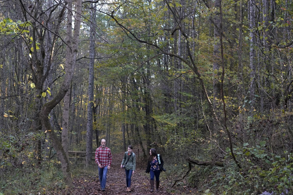 Olivia Chaffin, center, walks in the woods with her parents, Doug, left, and Kim Chaffin, as Olivia works on a Girl Scout photography merit badge in J...
