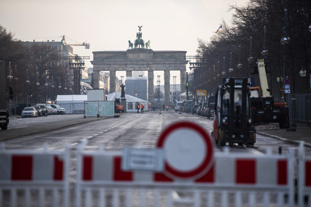The street leading to the Brandenburg Gate in Berlin, Germany is seen closed on Thursday Dec. 29, 2020 as set-up work starts for the digital New Year'...