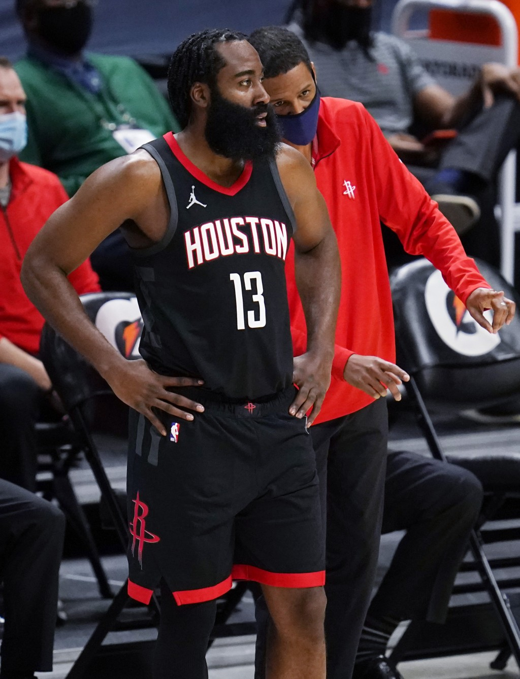 Houston Rockets guard James Harden confers with coach Stephen Silas during the second half of the team's NBA basketball game against the Denver Nugget...