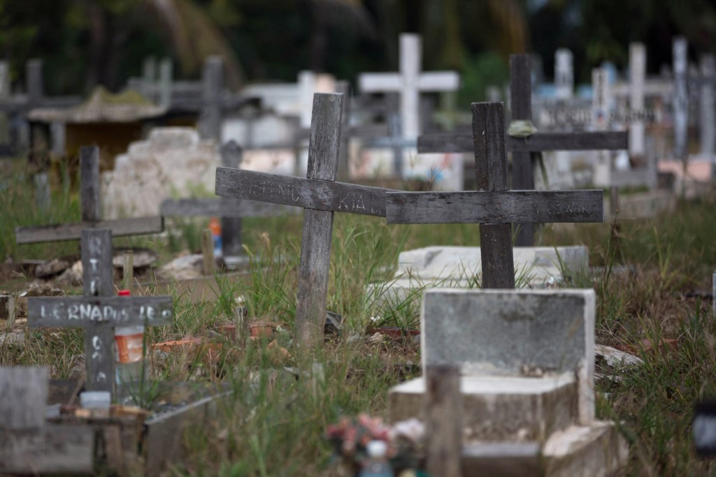 Crosses stand in a cemetery in Tawau, Malaysia, on Sunday, Dec. 9, 2018, where the grandchild and husband of Anna, 45, a migrant worker from Indonesia...