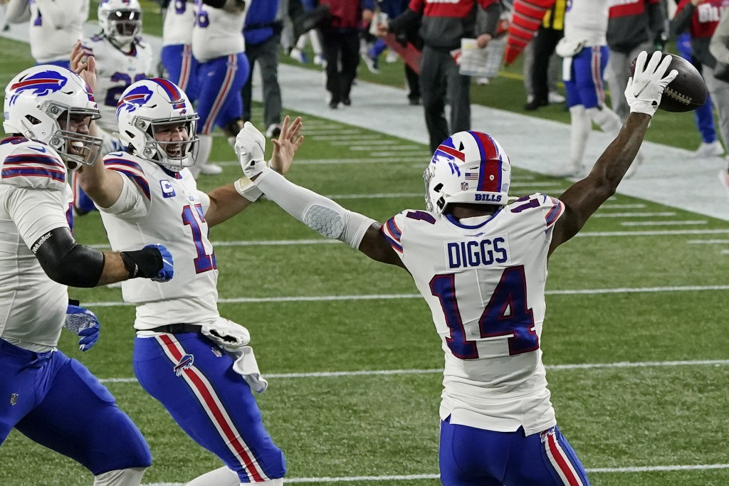 Buffalo Bills quarterback Josh Allen, second from left, celebrates his touchdown pass to Stefon Diggs, right, in the first half of an NFL football gam...