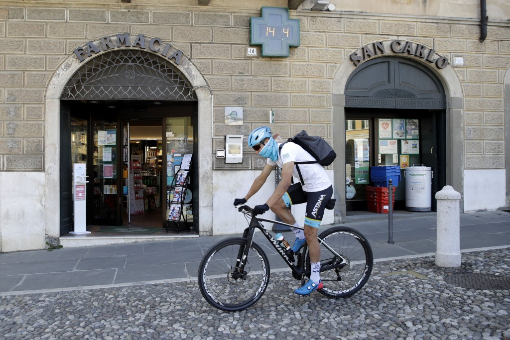 FILE - Italian professional cyclist Davide Martinelli rides his bike after collecting medicine at a pharmacy to be delivered to residents in Rovato, n...