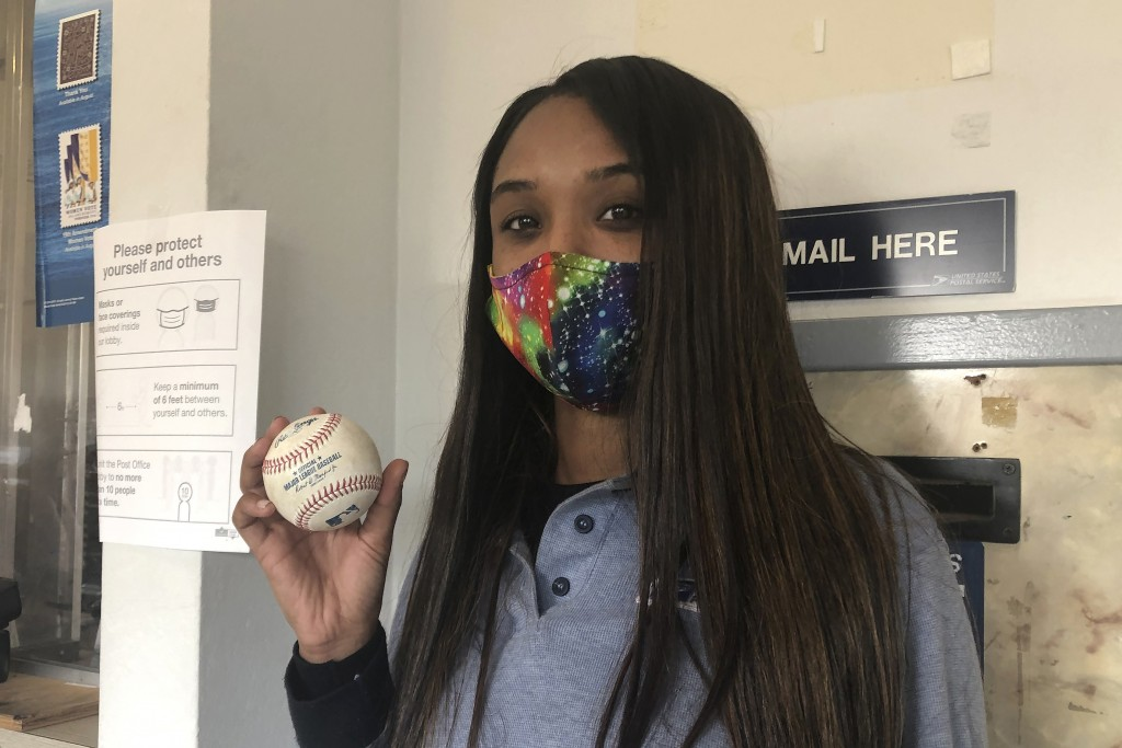 FILE - U.S. Postal Service worker Tionne Eitz holds a foul ball gift in Alameda, Calif., in this Monday, Sept. 21, 2020, file photo. Catching a foul b...