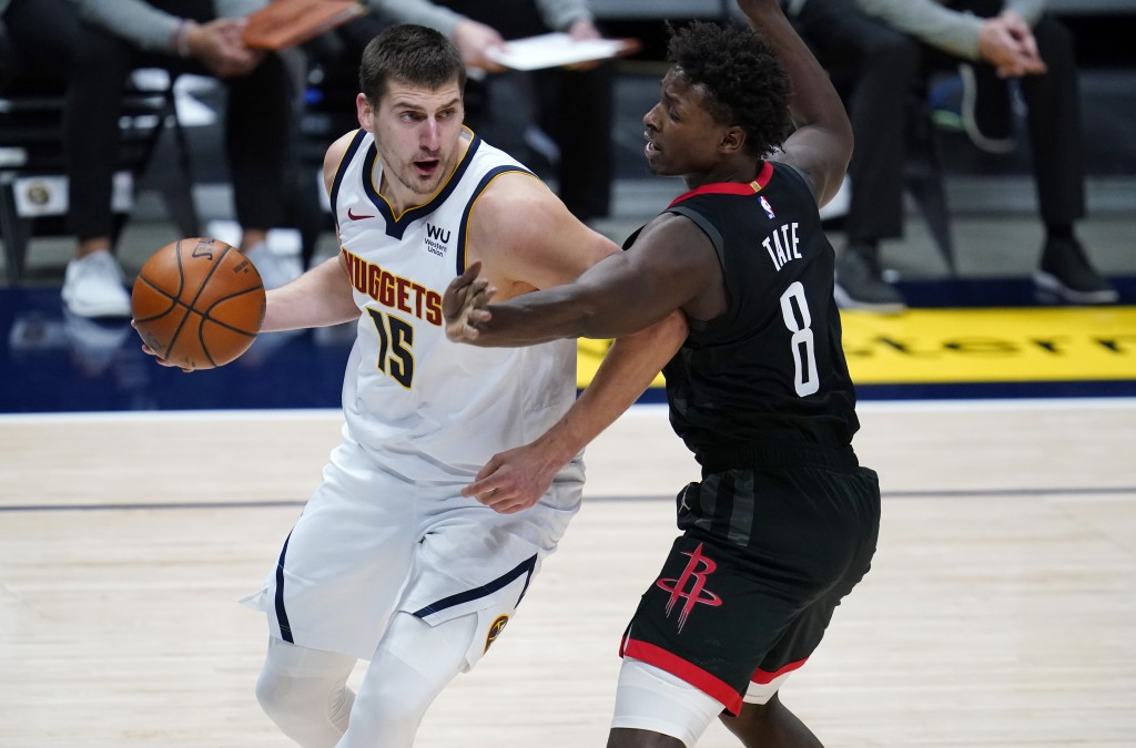 Denver Nuggets center Nikola Jokic, left, drives past Houston Rockets forward Jae'Sean Tate in the first half of an NBA basketball game, Monday, Dec. ...