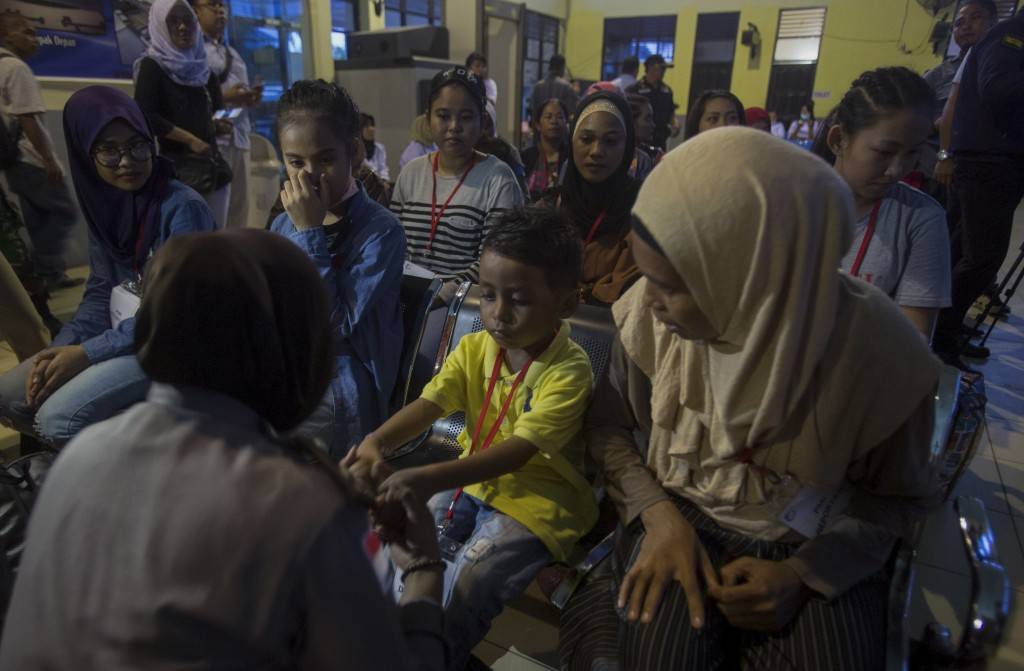 A police officer plays with a child deported with his Indonesian family for working illegally in Malaysia, at an immigration office processing center ...