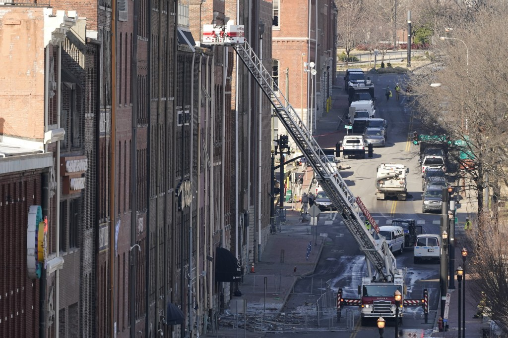 Firefighters ride in an aerial ladder as they inspect buildings damaged in a Christmas Day explosion Monday, Dec. 28, 2020, in Nashville, Tenn. Federa...