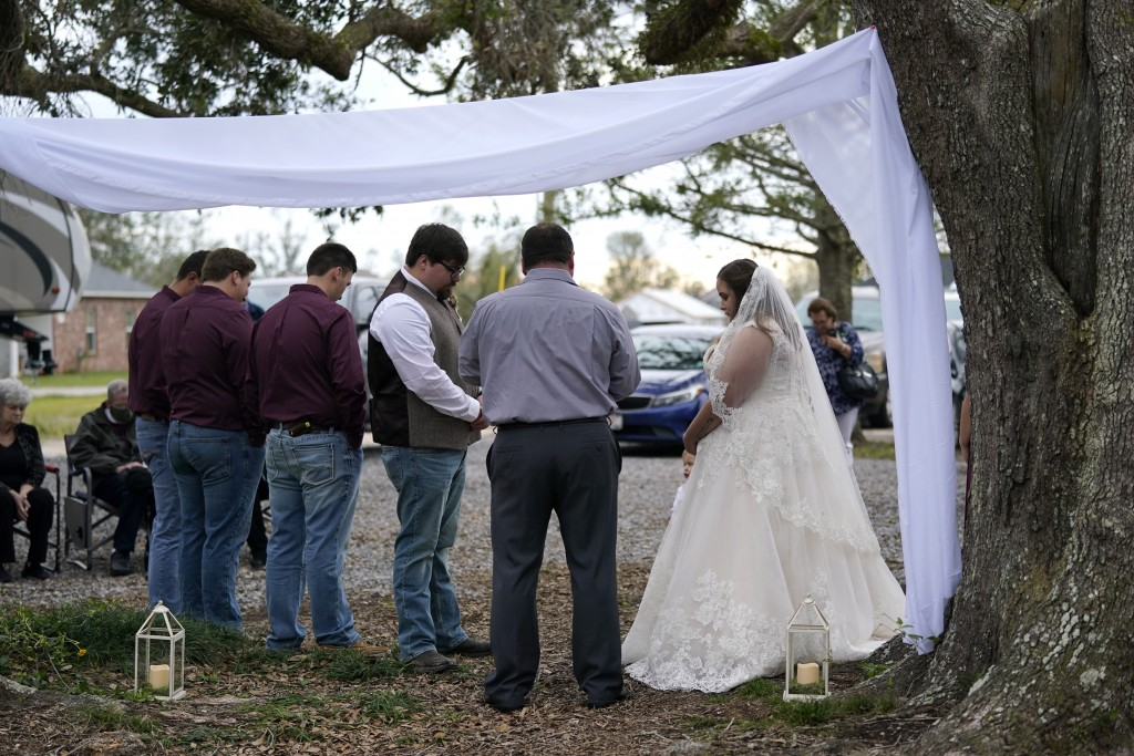Emily and Taylor Pascale exchange wedding vows outside the home of Taylor's parents, Friday, Dec. 4, 2020, in Grand Lake, La., which was heavily damag...