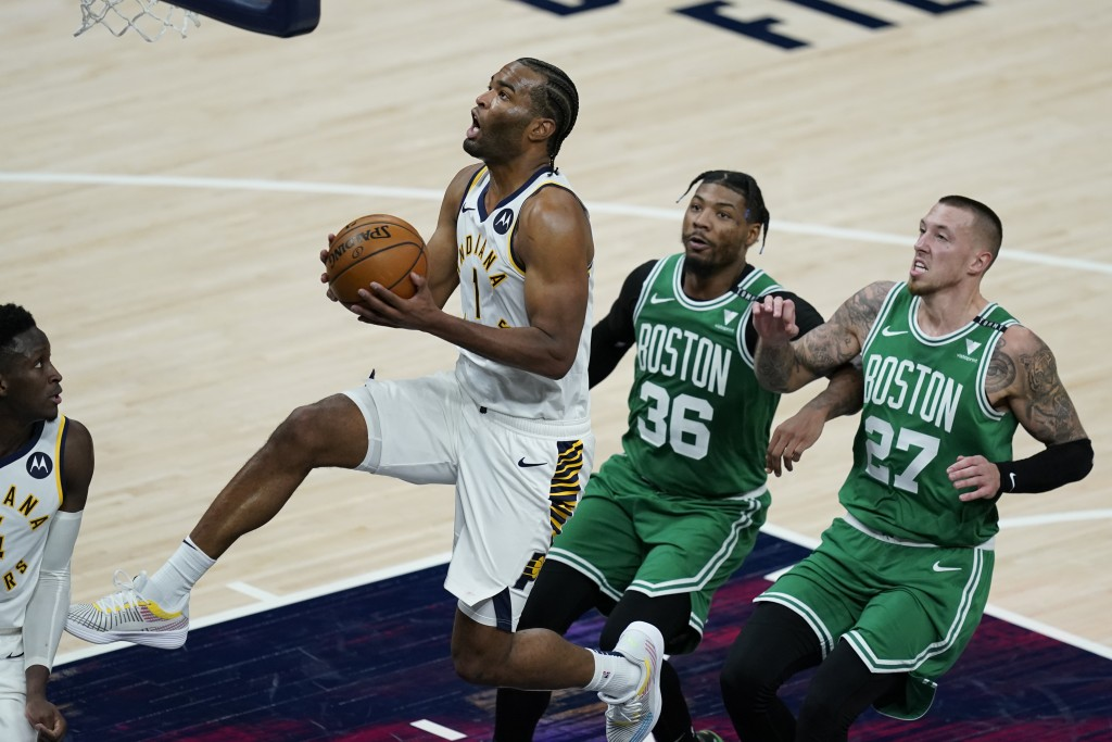 Indiana Pacers' T.J. Warren (1) goes to the basket as Boston Celtics' Marcus Smart (36) and Daniel Theis (27) trail during the second half of an NBA b...