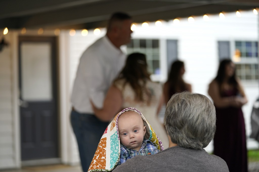 Theresa Kitfield holds her great grandson Beau Kitifield as her granddaughter Emily Pascale dances with her father, Eric Kitfield, after her wedding t...