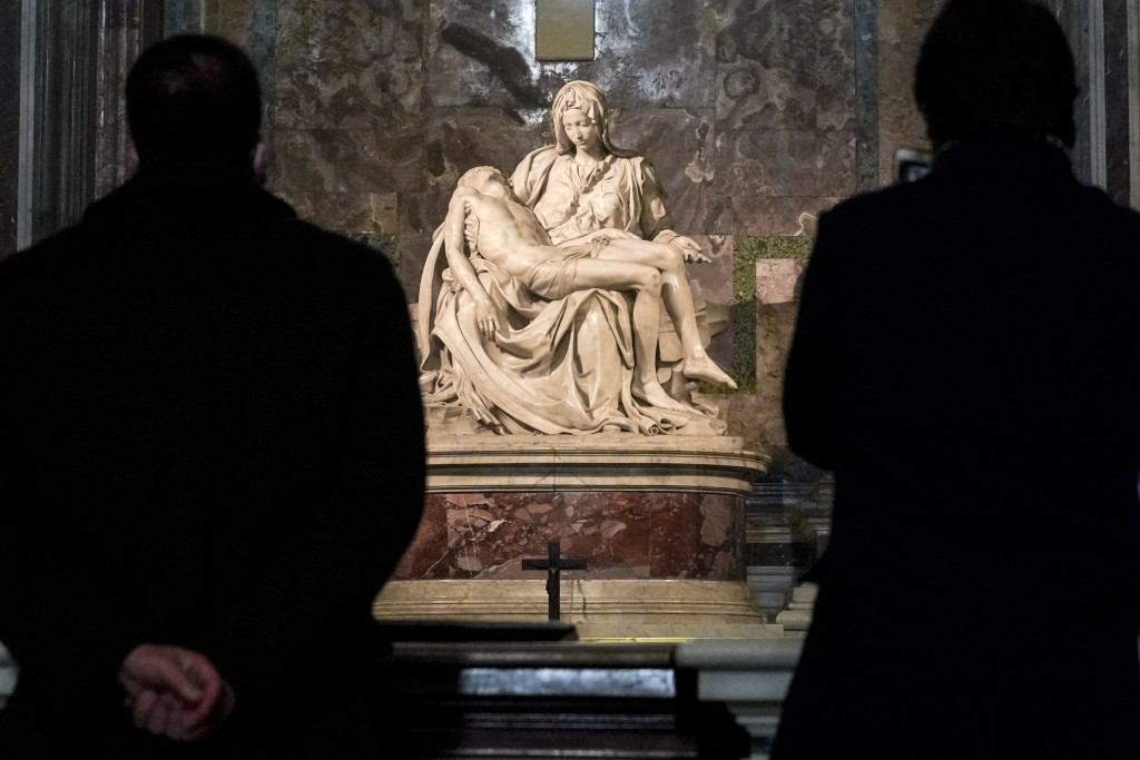 """Visitors admire the marble sculpture """"The Piety"""", made in 1499 by Italian sculptor Michelangelo Buonarroti, inside St. Peter's Basilica, at the Vatica..."""