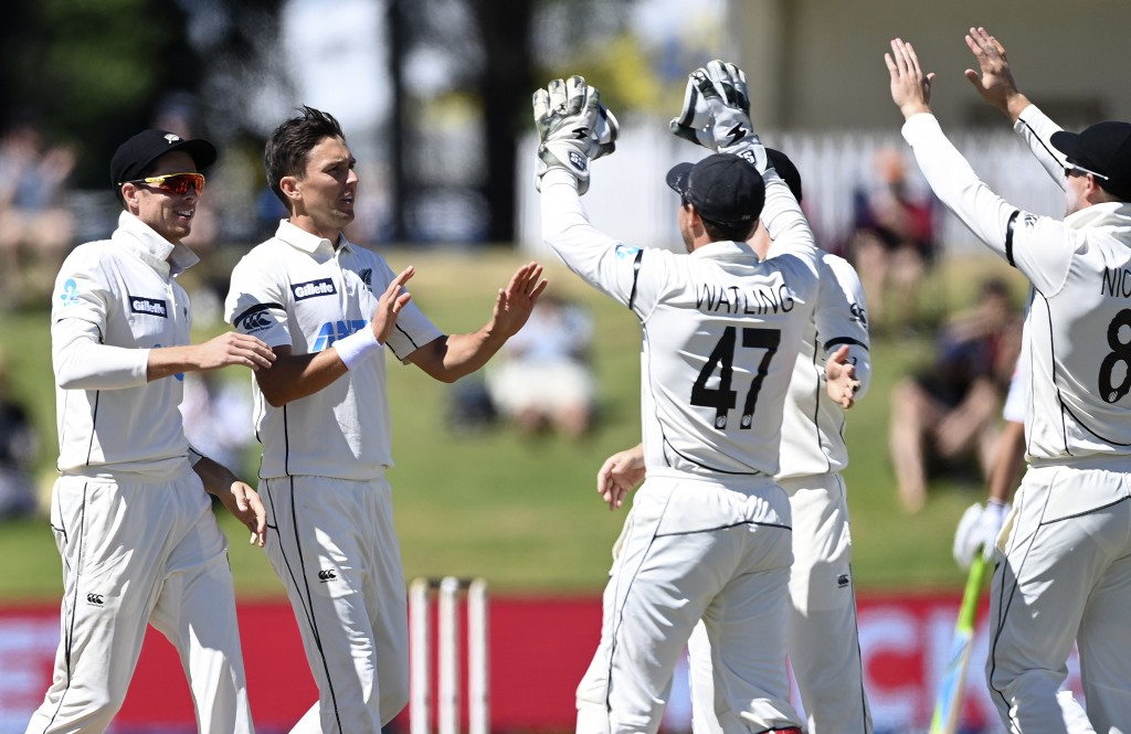 New Zealand's Trent Boult, second left, celebrates with teammates after taking the wicket of Pakistan batsman Azhar Ali during play on the final day o...