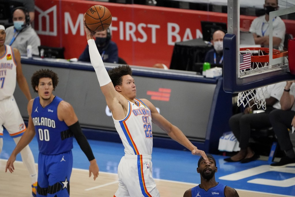 Oklahoma City Thunder forward Isaiah Roby (22) goes up for a dunk between Orlando Magic forward Aaron Gordon (00) and guard Terrence Ross during the s...
