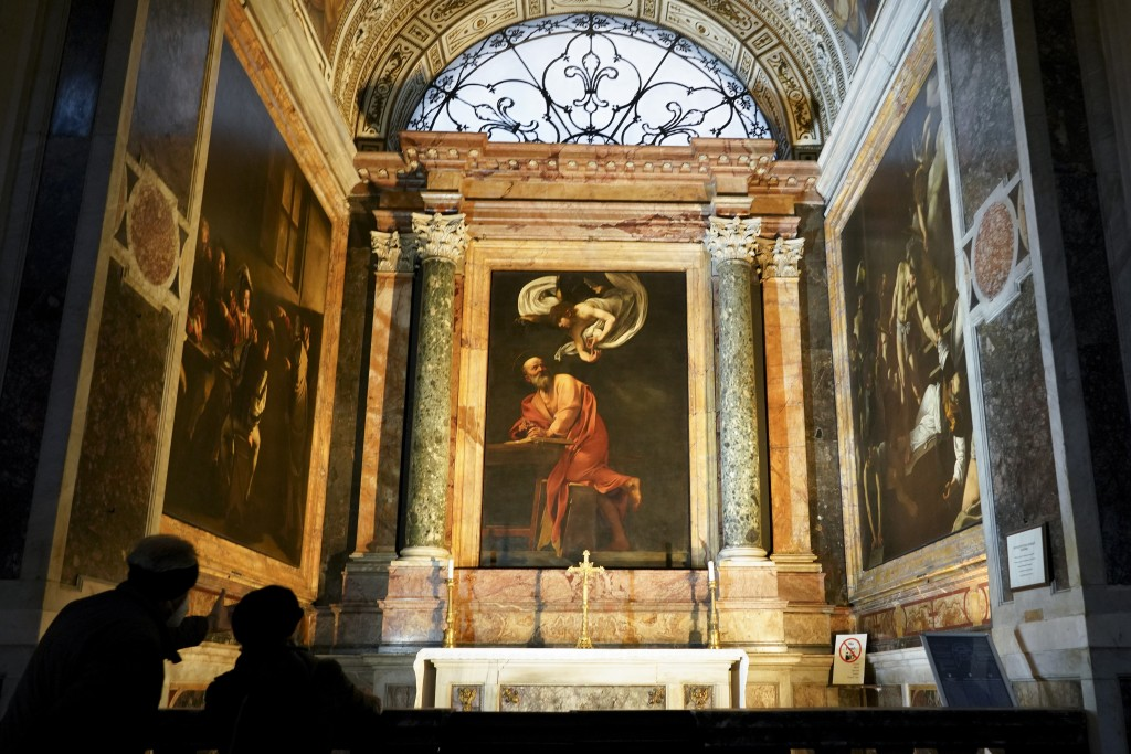 Visitors admire a cycle of paintings by 16th century artist Michelangelo Merisi, known as Caravaggio, on the life of St.Matthew, inside the Contarelli...