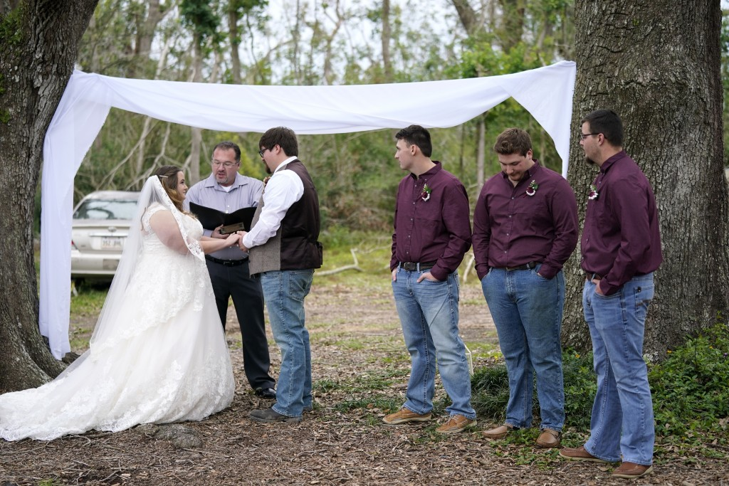 Emily and Taylor Pascale exchange their wedding vows outside the home of Taylor's parents, Friday, Dec. 4, 2020, in Grand Lake, La., which was heavily...